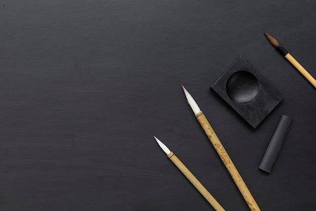 Traditioneller schreibpinsel der nahaufnahme japan auf schwarzem tisch. draufsicht. flach liegen