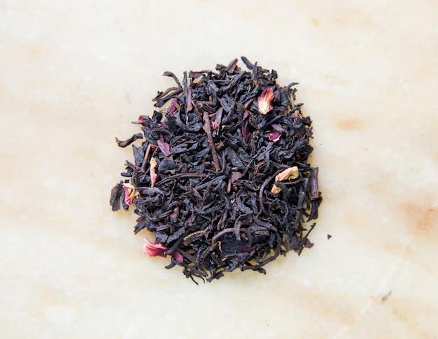 Traditioneller schwarzer tee mit blütenblättern nahaufnahmefoto für das menü