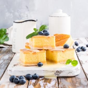 Traditioneller selbst gemachter gebackener puddingkuchen mit vanillepuddingcreme und -blaubeeren. gesundes dessert.