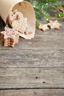 Traditioneller selbst gemachter weihnachtslebkuchenzucker, der im papierumschlag auf hölzernem bereift.