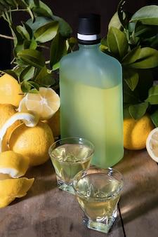 Traditioneller selbst gemachter zitronenlikör limoncello und frische zitrusfrucht auf dem alten hölzernen brett