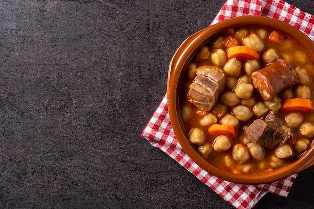 Traditioneller spanischer cocido madrileo in schüssel auf schwarzem hintergrund