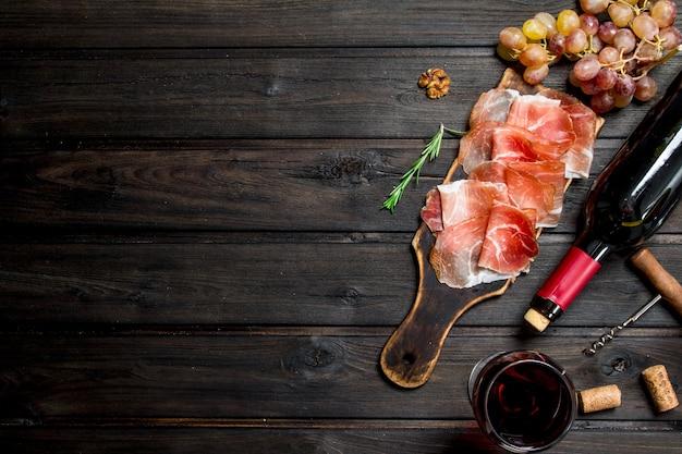 Traditioneller spanischer schinken mit rotwein auf einem rustikalen tisch.