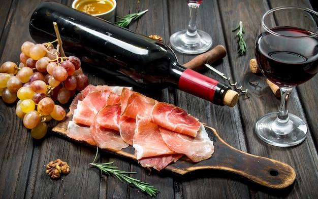Traditioneller spanischer schinken mit trauben und rotwein. auf einem hölzernen hintergrund.