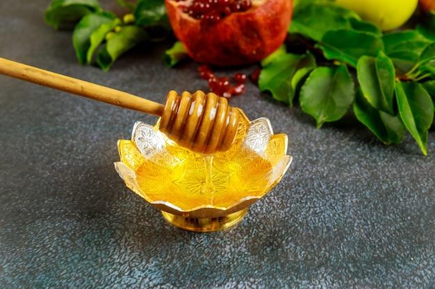 Traditioneller süßer honig mit holzstab und früchten für jüdischen feiertag rosh hashanah.