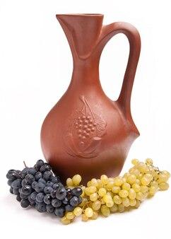 Traditioneller tonkrug für wein mit weintrauben