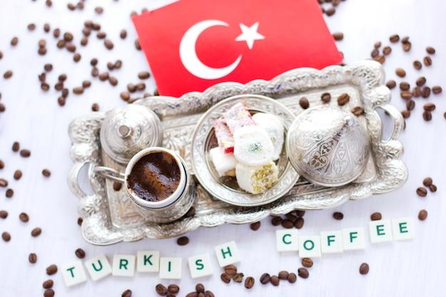 Traditioneller türkischer kaffee und bonbons im tafelsilber mit flagge von der türkei. schriftzug türkischer kaffee