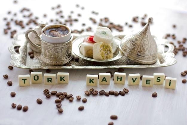 Traditioneller türkischer kaffee und süßigkeiten in besteck. schriftzug - türkischer kaffee - in türkischer sprache