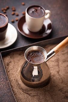 Traditioneller türkischer kaffee zubereitet auf heißem sand