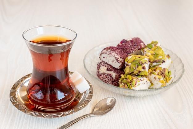 Traditioneller türkischer tee in einem glas mit süßigkeiten und einem löffel