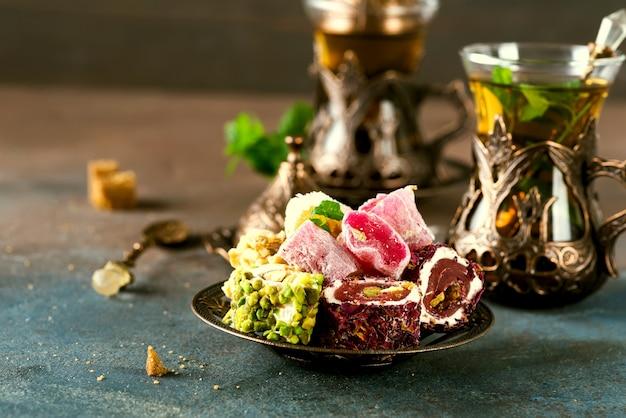 Traditioneller türkischer tee mit tadellosen blättern und bonbons in einem traditionellen glas auf beton