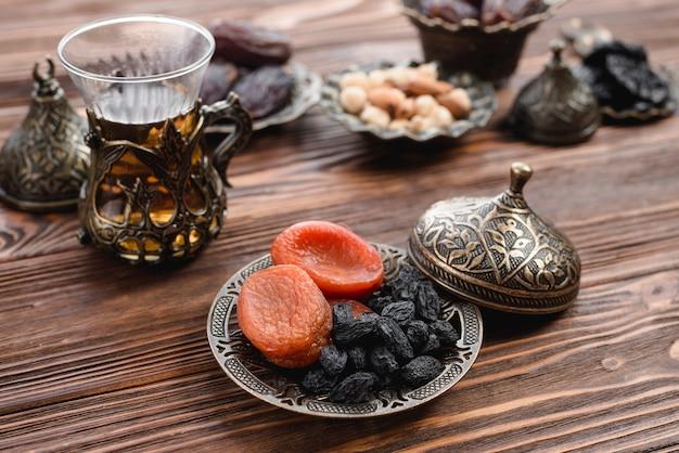 Traditioneller türkischer tee und trockenfrüchte auf metallischem behälter über dem holztisch