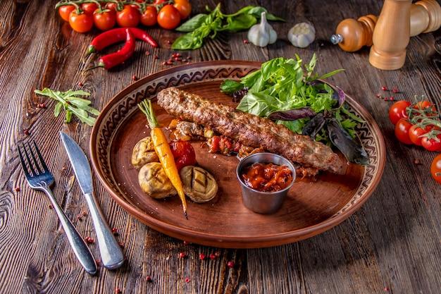 Traditioneller türkischer und arabischer ramadan mischen kebab-teller, kebab-lamm und rindfleisch mit gebackenem gemüse, pilzen und tomatensauce, nahaufnahme, horizontales foto