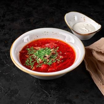 Traditioneller ukrainischer russischer borschtsch. schüssel rote-bete-wurzel-suppe borschtsch mit weißer sahne. köstliche rote-bete-suppe. traditionelle ukrainische küche