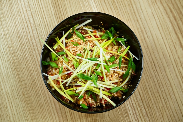 Traditioneller vietnamesischer streetfood-reis mit gemüse und fleisch in einer schwarzen schüssel