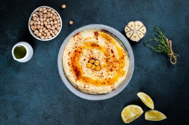 Traditioneller vorspeise hummus aus dem nahen osten, serviert mit zitrone und tahini, gewürzt mit extra nativem olivenöl und paprika in keramikplatte. östliches gericht. vegetarisches gericht. traditioneller dip mit kichererbsen.