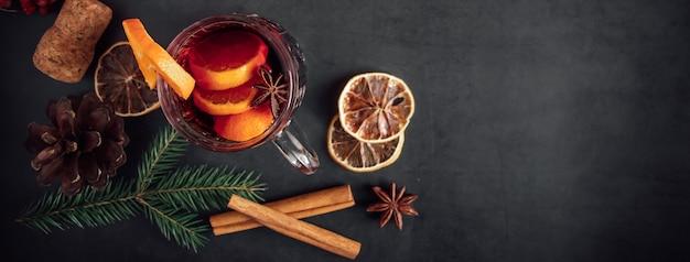 Traditioneller weihnachtlicher glühwein. heißes getränk mit gewürzen in der glasschale auf einem dunklen hintergrund.