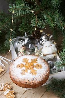 Traditioneller weihnachtsfruchtkuchen auf einem kasten mit weihnachtsspielwaren und -tannenzweigen.
