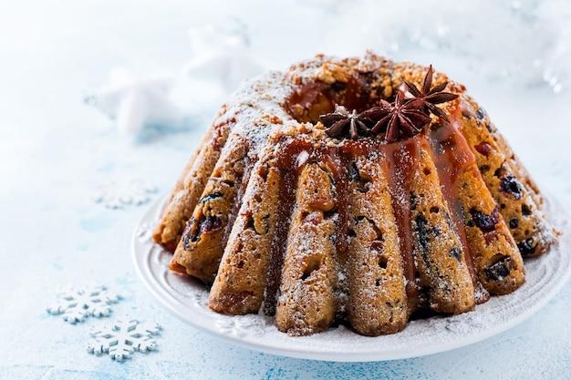 Traditioneller weihnachtsfruchtkuchen, pudding auf weißem teller. platz kopieren.
