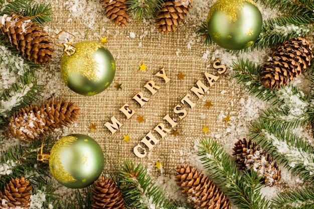 Traditioneller weihnachtshintergrund mit weihnachtskugeln, kegeln und fichtenzweigen. ausgelegte holzbuchstaben, mit dem wunsch nach frohen weihnachten.