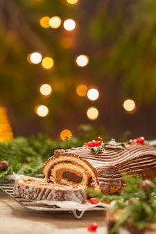 Traditioneller weihnachtskuchen schokolade yule log mit festlicher dekoration