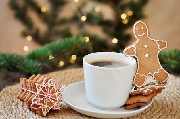 Traditioneller weihnachtslebkuchen-zuckerguss geformt wie ein lustiger kleiner mann und eine schale heißer espresso auf hölzernem.