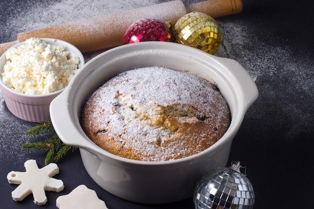 Traditioneller weihnachtsquarkkuchen mit rosinen in einer auflaufform auf schwarzem hintergrund mit mehl
