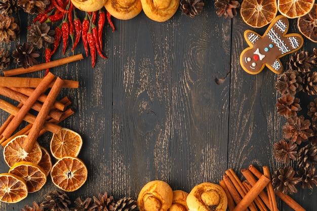 Traditioneller weihnachtsrahmen mit gewürzen, spekulatiuskeksen, sternkeksen und verschiedenen nüssen, die mit getrockneter orange um zentralen kopyspace auf einem rustikalen holzhintergrund verziert werden
