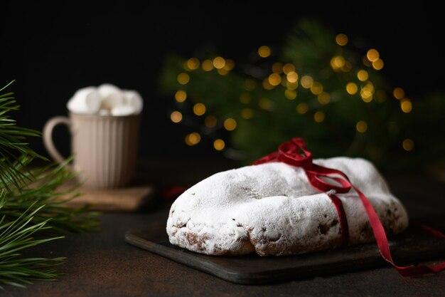 Traditioneller weihnachtsstollen verziertes feiertagsseil auf einem festlich gedeckten tisch mit girlandenkaffeetasse