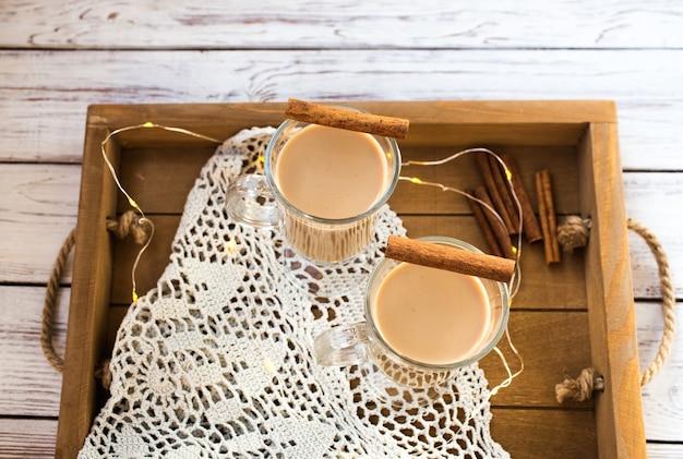 Traditioneller winter-eierlikör im glasbecher mit milch, rum und zimt, weihnachtsdekorationen.