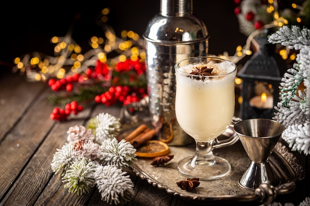 Traditioneller wintereierlikör im glasbecher mit milchrum und zimt-weihnachtsdekorationen