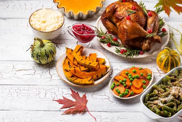 Traditionelles abendessen am erntedankfest. gebackener truthahn, kürbiskuchen, auflauf mit grünen bohnen und kartoffelpüree