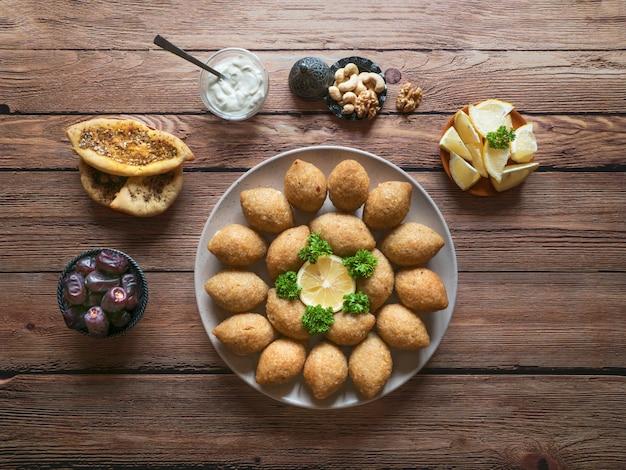 Traditionelles arabisches kibbeh mit lamm und pinienkernen. draufsicht.