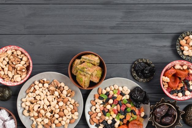 Traditionelles arabisches ramadan-baklava; trockenfrüchte und nüsse auf holztisch gedient