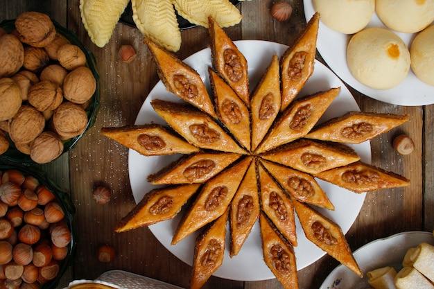 Traditionelles aserbaidschan-feiertagsplätzchenbaklava auf weißer platte auf dem rustikalen hintergrund