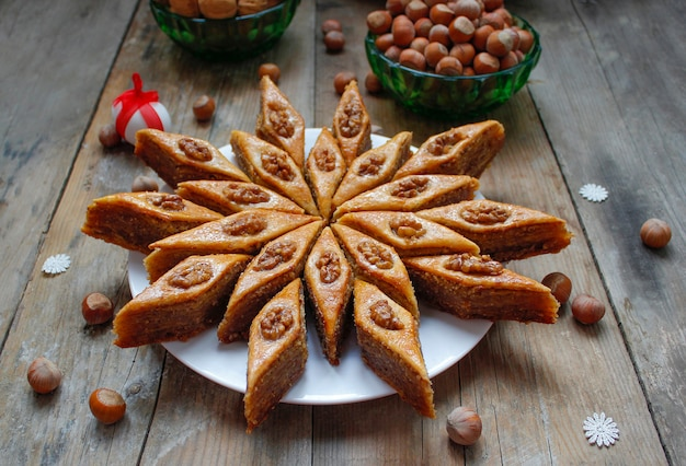 Traditionelles aserbaidschan-feiertagsplätzchenbaklava auf weißer platte auf dem rustikalen mit nüssen