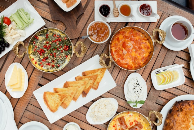 Traditionelles aserbaidschanisches frühstück mit eiteller, pfannkuchen, frischem salat, stau, käse, honig