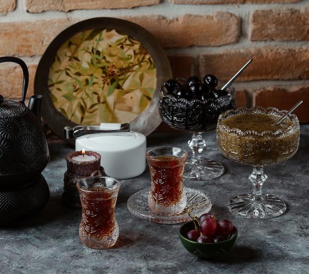Traditionelles aserbaidschanisches teeservice für zwei personen mit verschiedenen konfitüren und trauben