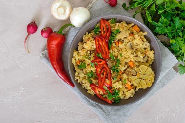 Traditionelles asiatisches gericht - pilaw mit fleisch, pilzen und pfeffer capi in einer schüssel