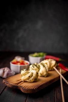 Traditionelles asiatisches lebensmittel auf hölzernem brett mit knoblauch und essstäbchen