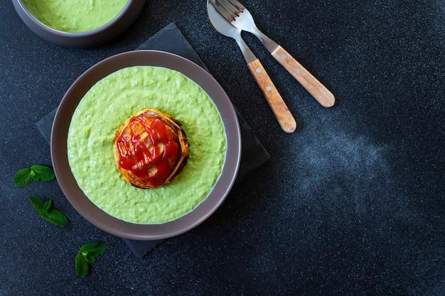 Traditionelles australisches gericht namens pie floater. grüne erbsensuppe serviert mit australischer fleischpastete. australische küche. schwarzer hintergrund. draufsicht. speicherplatz kopieren