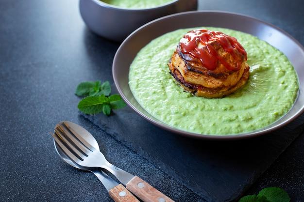 Traditionelles australisches gericht namens pie floater. grüne erbsensuppe serviert mit australischer fleischpastete. australische küche. schwarzer hintergrund. nahansicht. speicherplatz kopieren