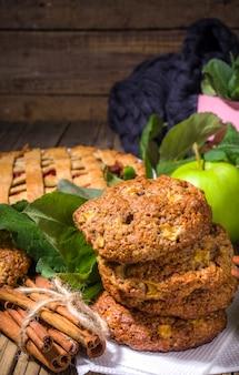 Traditionelles backen im herbst, hausgemachter apfelkuchen und apfelkuchen-haferflocken-zimt-kekse, halloween-danksagung, herbstbacken, gemütliches backen auf holzhintergrund