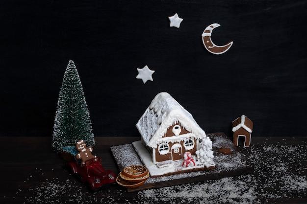 Traditionelles backen. lebkuchenhaus, lebkuchensterne, kleiner weihnachtsbaum und spielzeugauto.