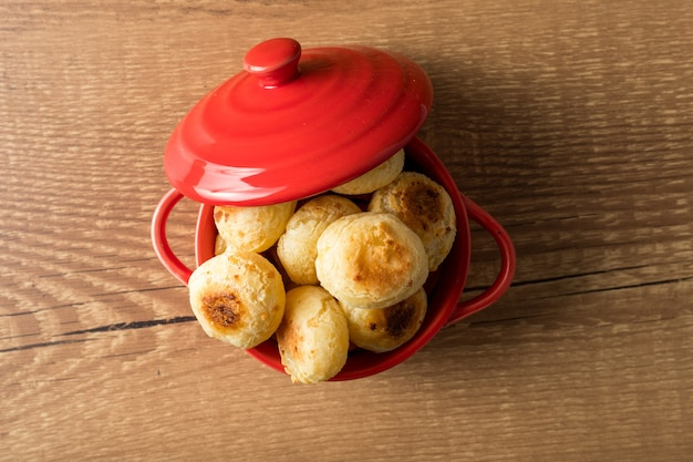 Traditionelles brasilianisches snack-käse-brot in einem rustikalen roten kochtopf