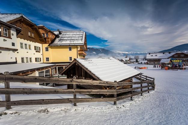 Traditionelles chalet und skigebiet in den österreichischen alpen mit schnee bedeckt