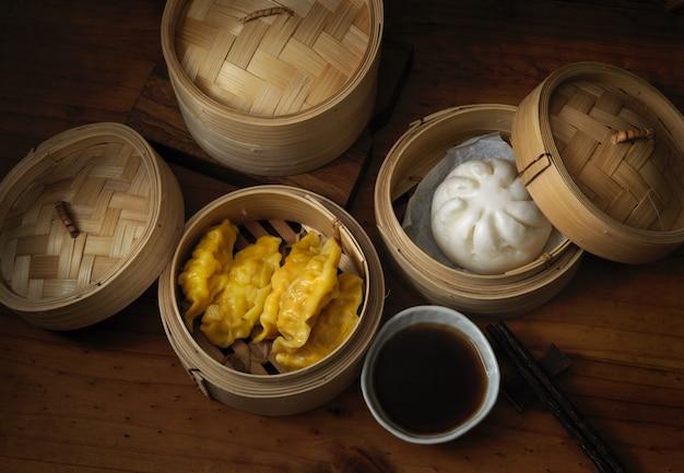 Traditionelles chinesisches essen, gedämpfte knödel, die auf bambussitzer auf holztisch dienen