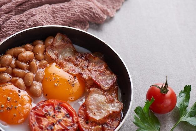 Traditionelles englisches frühstück in einer pfanne mit spiegeleiern, speck, bohnen und gegrillten tomaten.