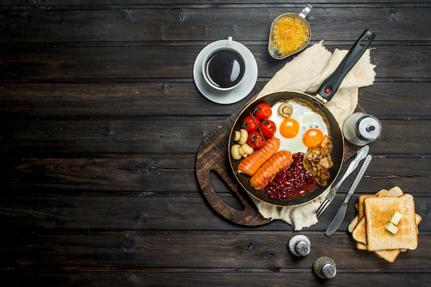 Traditionelles englisches frühstück mit einer auswahl an speisen und aromatischem kaffee. auf einer holzoberfläche.