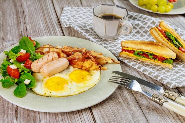 Traditionelles englisches frühstück mit speck, eiern, würstchen, salat und gegrilltem käsetoast.